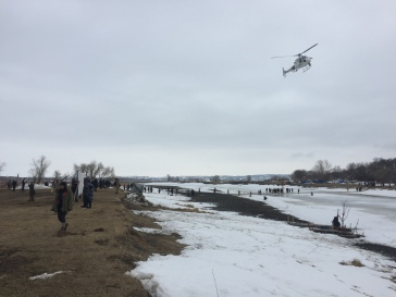 Customs and Border Patrol helicopter over the Cannonball River. To the left is Rosebud, to the right is former Oceti Sakowin.