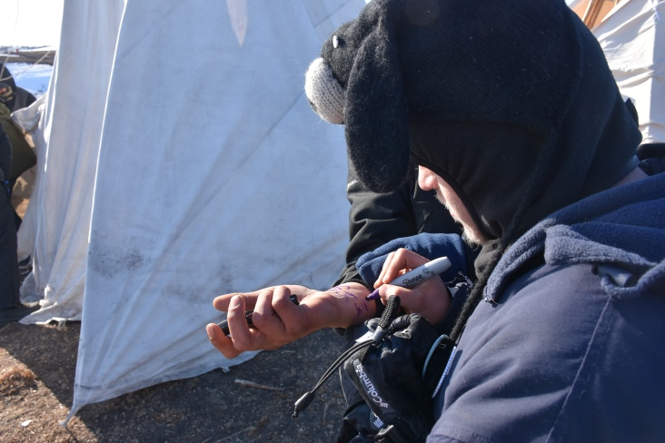 Water Protector writing the number for legal support prior to arrest.